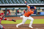 Houston Astros' Yuli Gurriel (10) watches his RBI double in front of Los Angeles Angels catcher Jason Castro during the fourth inning of the first game of a baseball doubleheader Tuesday, Aug. 25, 2020, in Houston. (AP Photo/Michael Wyke)