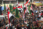 Protesters hold Popular Mobilization forces and Iraqi flags and chanting religious slogans march towards Tahrir Square in Baghdad, Iraq, Friday, Dec. 6, 2019. (AP Photo/Hadi Mizban)