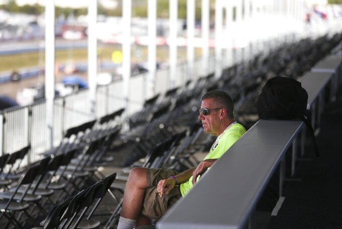 Jon Jenney, sits alone with no fans in the stand while working in the VIP area overlooking pit lane, at the IndyCar Grand Prix of St. Petersburg, Friday, March 13, 2020 in St. Petersburg. NASCAR and IndyCar have postponed their weekend schedules at Atlanta Motor Speedway and St. Petersburg, due to concerns over the COVID-19 pandemic. (Dirk Shadd/Tampa Bay Times via AP)