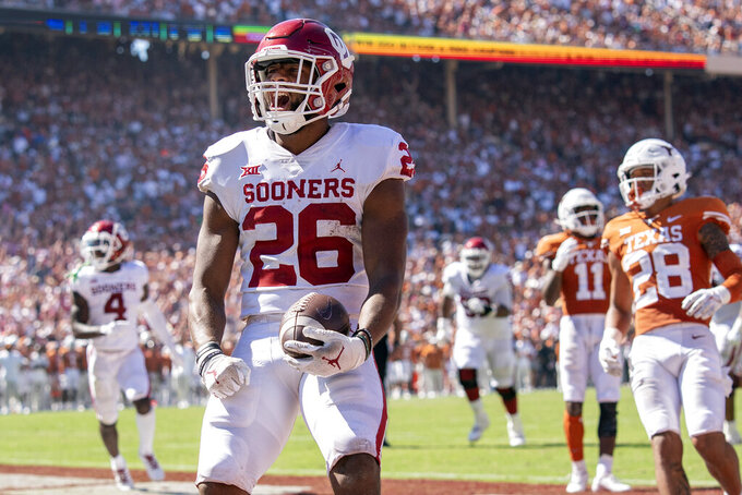 Oklahoma running back Kennedy Brooks (26) runs in for a touchdown against Texas during the fourth quarter of an NCAA college football game at the Cotton Bowl, Saturday, Oct. 9, 2021, in Dallas. Oklahoma won 54-48. (AP Photo/Jeffrey McWhorter)