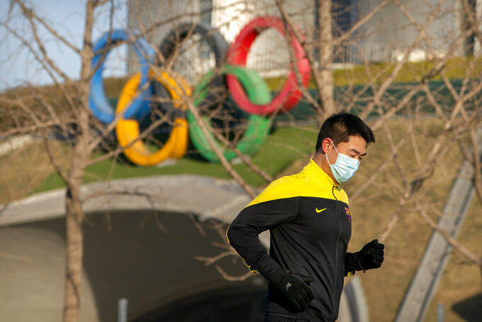 """A man wearing a face mask to protect against the spread of the coronavirus jogs past Olympic rings displayed outside the Olympic Tower in Beijing, Tuesday, Feb. 2, 2021. The 2022 Beijing Winter Olympics will open a year from now. Most of the venues have been completed as the Chinese capital becomes the first city to hold both the Winter and Summer Olympics. Beijing held the 2008 Summer Olympics. But these Olympics are presenting some major problems. They are already scarred by accusations of rights abuses including """"genocide""""against more than 1 million Uighurs and other Muslim ethnic groups in western China. (AP Photo/Mark Schiefelbein)"""