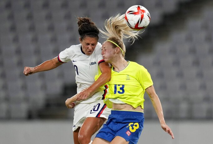 United States' Carli Lloyd, left, and Sweden's Amanda Ilestedt, right, go for a header during a women's soccer match at the 2020 Summer Olympics, Wednesday, July 21, 2021, in Tokyo. (AP Photo/Ricardo Mazalan)