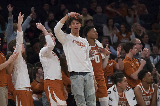 Texas players on the bench react during the second half of a semifinal college basketball game in the National Invitational Tournament against TCU, Tuesday, April 2, 2019, at Madison Square Garden in New York. Texas won 58-44. (AP Photo/Mary Altaffer)