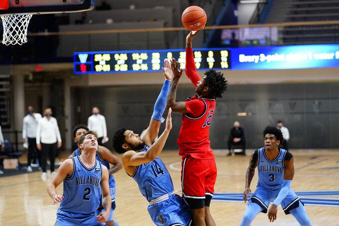 St. John's Vince Cole (15) goes up for a shot against Villanova's Caleb Daniels (14) during the second half of an NCAA college basketball game, Tuesday, Feb. 23, 2021, in Villanova, Pa. (AP Photo/Matt Slocum)