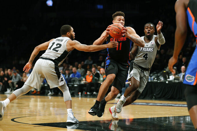 Florida forward Keyontae Johnson (11) drives against Providence guards Luwane Pipkins (12) and Maliek White (4) during the first half of an NCAA college basketball game at Barclays Center, Tuesday, Dec. 17, 2019, in New York. (AP Photo/Michael Owens)