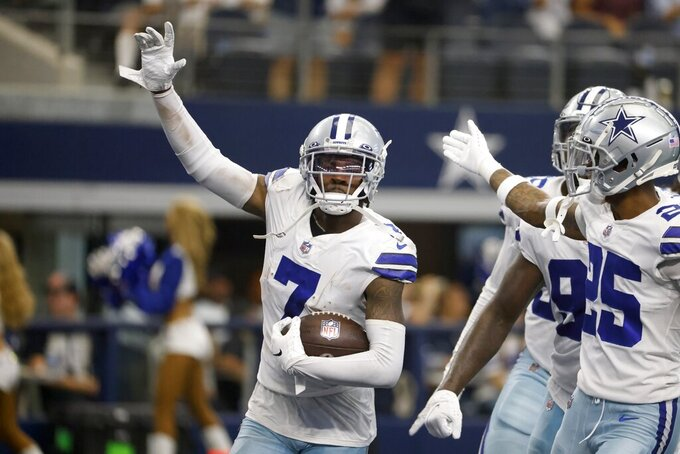 Dallas Cowboys cornerback Trevon Diggs (7), Nahshon Wright (25) and others celebrate Diggs intercepting a Carolina Panthers' Sam Darnold pass in the second half of an NFL football game in Arlington, Texas, Sunday, Oct. 3, 2021. (AP Photo/Ron Jenkins)