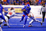 Boise State quarterback Jaylon Henderson, center, runs through the the arm tackle attempts of New Mexico safety Letayveon Beaton, left, and New Mexico linebacker Alex Hart, right, during the second half of an NCAA college football game Saturday, Nov. 16, 2019, in Boise, Idaho. Boise State won 42-9. (AP Photo/Steve Conner)