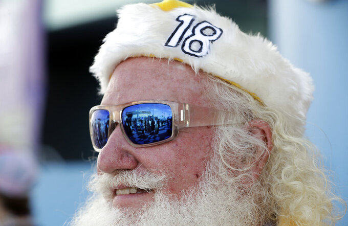 Victory lane is reflected in the sunglasses of a fan wearing a hat for driver Kyle Busch (18) during the NASCAR Series Championship auto race at the Homestead-Miami Speedway, Sunday, Nov. 18, 2018, in Homestead, Fla. (AP Photo/Lynne Sladky)