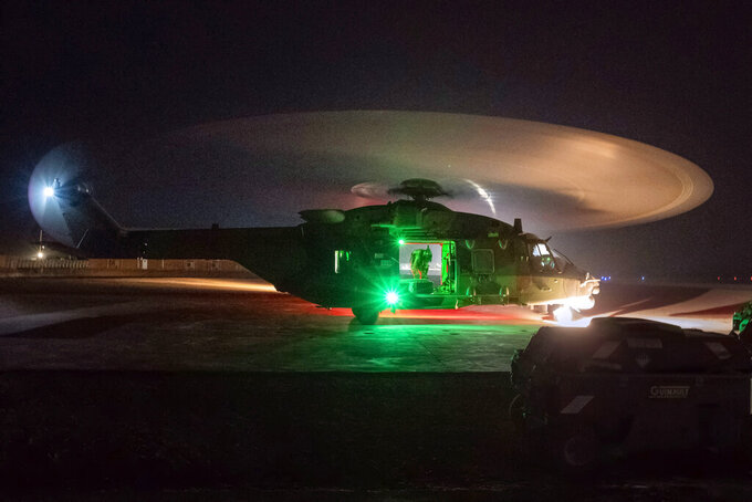 A French Barkhane force Caiman transport helicopter lands following a night mission in Gao, Mali, Monday June 7, 2021. France has suspended joint military operations with Malian forces until the junta led by Col. Assimi Goita, who retook control of Mali's transitional government May 24, complies with international demands to restore civilian rule. (AP Photo/Jerome Delay)