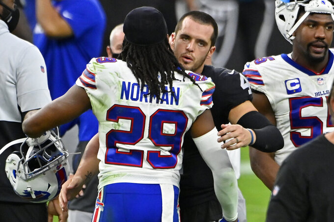 Las Vegas Raiders quarterback Derek Carr (4) embraces Buffalo Bills cornerback Josh Norman (29) after an NFL football game, Sunday, Oct. 4, 2020, in Las Vegas. The Bills won 30-23. (AP Photo/David Becker)