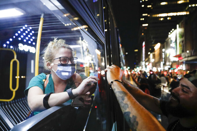 A healthcare professional riding a bus, left, greets protesters as they break curfew and march along 34th Street, Thursday, June 4, 2020, in the Manhattan borough of New York. Protests continued following the death of George Floyd, who died after being restrained by Minneapolis police officers on May 25. (AP Photo/John Minchillo)