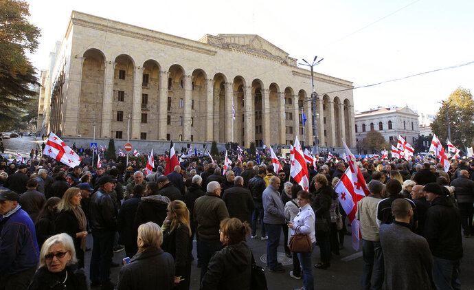 Demonstrators gather at the Georgian parliament building to protest against government failures to pass election-reform constitutional measures, in Tbilisi, Georgia, Sunday, Nov. 17, 2019.  Some hundreds of demonstrators gathered outside the parliament building to protest after the government backed down on a promise to reform the election system that supports the ruling party. (AP Photo/Shakh Aivazov)