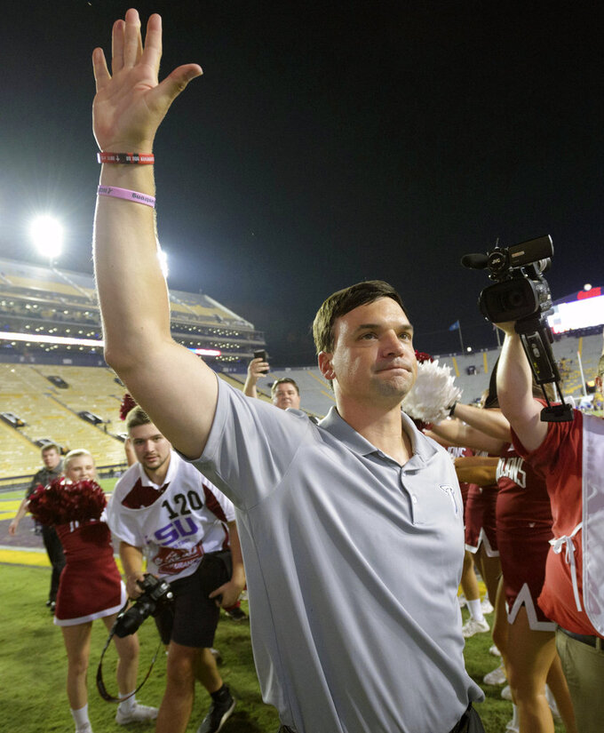 FILE - In this Sept. 30, 2017, file photo, Troy head coach Neal Brown celebrates his team's 24-21 victory over LSU in an NCAA college football game in Baton Rouge, La. West Virginia and Troy's Neal Brown are completing a deal to make him the next coach of the Mountaineers, two people familiar with the situation told The Associated Press on Friday, Jan. 4, 2018. The people spoke to AP on condition of anonymity because the contract was not yet final. (AP Photo/Matthew Hinton, File)