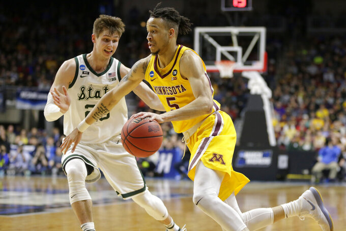 Minnesota's Amir Coffey (5) drives around Michigan State's Matt McQuaid (20) during the first half of a second round men's college basketball game in the NCAA Tournament, in Des Moines, Iowa, Saturday, March 23, 2019. (AP Photo/Nati Harnik)