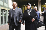 Aye Yozgat, right, and Ismail Yozgat, left, parents of NSU victim  Halit Yozgat, arrive outside the court in Munich, southern Germany, prior to the verdict Wednesday, July 11, 2018 before a court in Munich is due to conclude its five-year trial of the only known survivor of a far-right cell NSU suspected of killing nine people from ethnic minorities and a police officer, in a case that shocked Germany when it came to light in 2011. (Tobias Hase/dpa via AP)