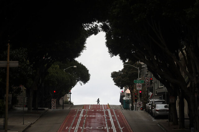 Pedestrians cross Cable Car tracks on Powell Street in San Francisco, Sunday, March 29, 2020. Californians endured a weekend of stepped-up restrictions aimed at keeping them home as much as possible while hospitals and health officials scrambled Sunday to ready themselves for a week that could see the feared dramatic surge in coronavirus cases. (AP Photo/Jeff Chiu)