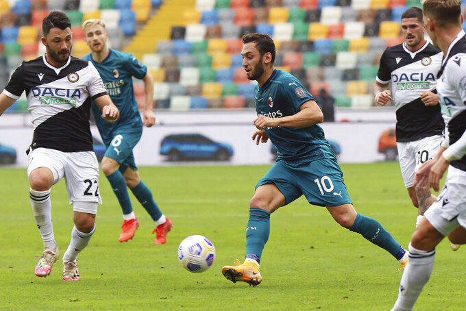 AC Milan's Hakan Calhanoglu goes for the ball during the Serie A soccer match between Udinese and AC Milan, at the Dacia Arena Stadium in Udine, Italy, Sunday, Nov. 1, 2020. (Andrea Bressanutti/LaPresse via AP)