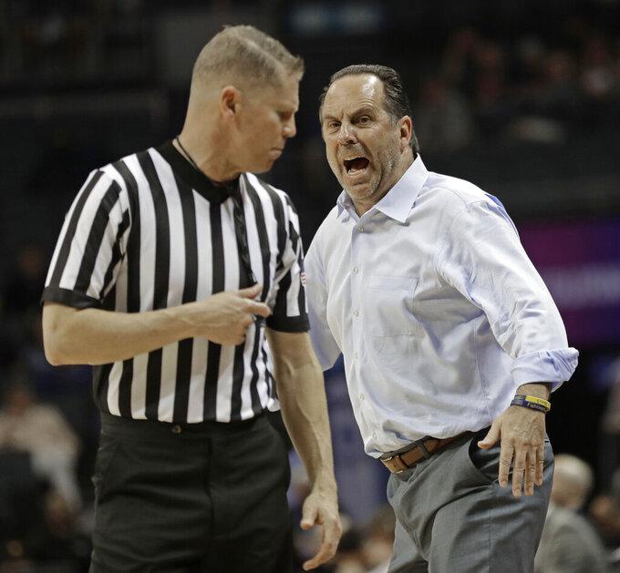 Notre Dame head coach Mike Brey, right, shouts at an official during the first half of an NCAA college basketball game against Louisville in the Atlantic Coast Conference tournament in Charlotte, N.C., Wednesday, March 13, 2019. (AP Photo/Nell Redmond)