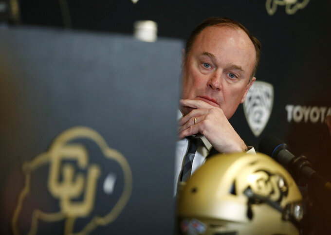 Colorado athletic director Rick George listens as Karl Dorrell talks at a news conference to announce that he is the new NCAA college head football coach at Colorado during a news conference Monday, Feb. 24, 2020, in Boulder, Colo. (AP Photo/David Zalubowski)