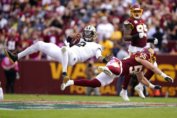 New Orleans Saints quarterback Jameis Winston (2) is flipped over by Washington Football Team linebacker Cole Holcomb (55) in the second half of an NFL football game, Sunday, Oct. 10, 2021, in Landover, Md. (AP Photo/Alex Brandon)