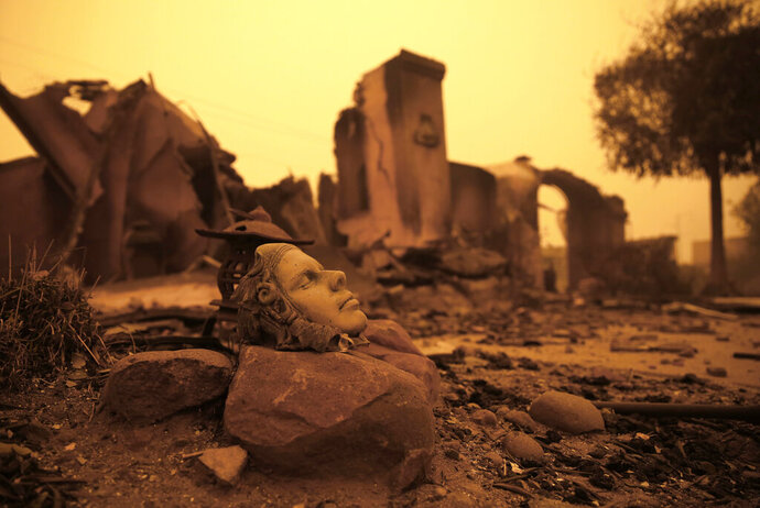 FILE - In this Nov. 9, 2018, file photo, a piece of statuary sits outside the burned remains of a home destroyed by the Camp Fire in Paradise, Calif. California officials said Tuesday, Nov. 19, 2019, that crews have finished removing millions of tons of debris left by a Northern California wildfire that killed 85 people and virtually annihilated a town. The Camp Fire was the deadliest and most destructive wildfire in state history. (AP Photo/Rich Pedroncelli, File)