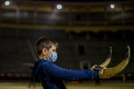Pupil Nicolas Sanz Luna, 10, holds a pair of plastic bull horns at the Bullfighting School at Las Ventas bullring in Madrid, Spain, Tuesday, Dec. 22, 2020. At this school children as young as 9 can begin learning this deadly dance of human and beast so closely associated with Spanish identity. The school was closed from March to August when Spain went into one of the world's strictest confinements to stem the spread of the COVID-19 pandemic.(AP Photo/Manu Fernandez)