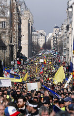 Yellow vest protesters march Saturday, Feb.16, 2019 in Paris. Yellow vest protesters are holding scattered demonstrations around Paris and the rest of France amid waning support for their movement. (AP Photo/Thibault Camus)
