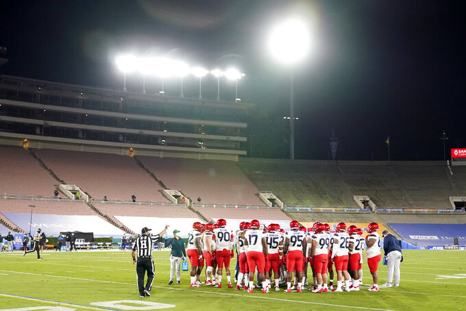Arizona players huddle in an empty Rose Bowl during the second half of an NCAA college football game against UCLA, Saturday, Nov. 28, 2020, in Pasadena, Calif. (AP Photo/Marcio Jose Sanchez)