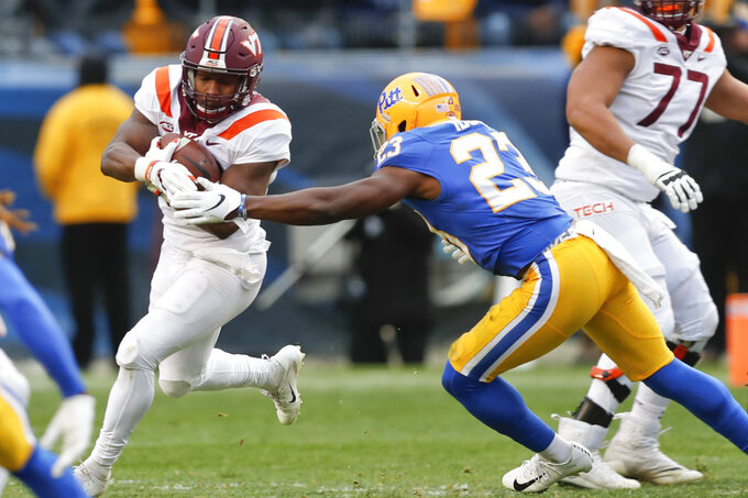 Virginia Tech running back Steven Peoples (32) runs away from Pittsburgh linebacker Oluwaseun Idowu (23) in the second quarter of an NCAA football game, Saturday, Nov. 10, 2018, in Pittsburgh. (AP Photo/Keith Srakocic)