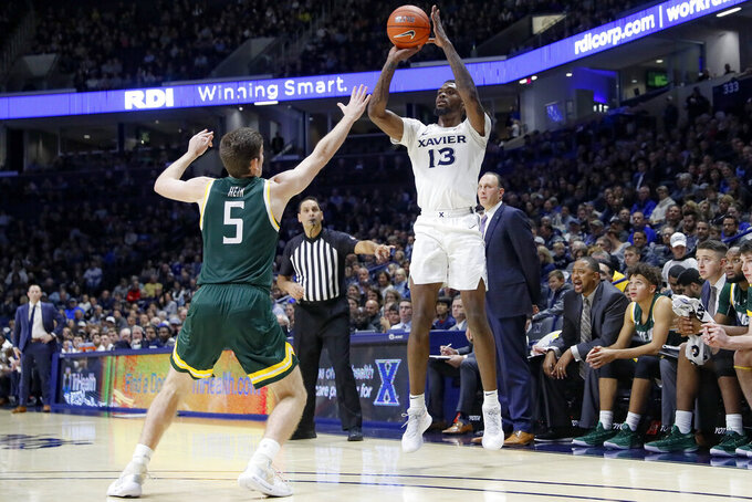 Xavier's Naji Marshall (13) shoots over Siena's Matt Hein (5) during the first half of an NCAA college basketball game Friday, Nov. 8, 2019, in Cincinnati. (AP Photo/John Minchillo)