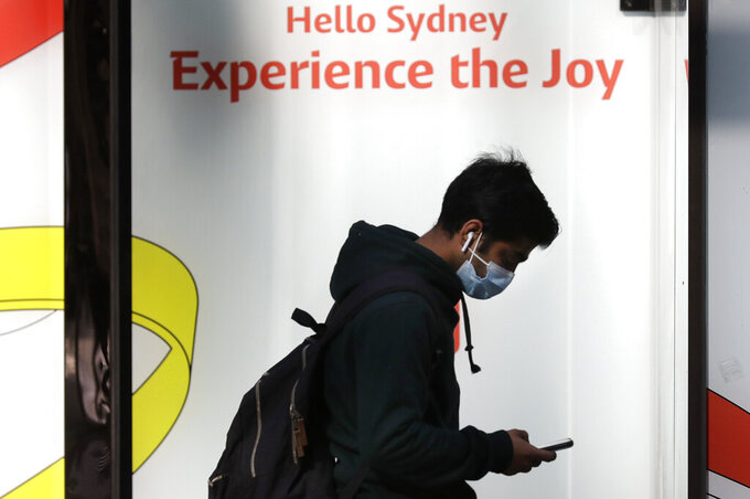 A man wears a mask as he walks in Sydney, Wednesday, July 7, 2021. Sydney's two-week lockdown has been extended for another week due to the vulnerability of an Australia population largely unvaccinated against COVID-19, officials said. (AP Photo/Rick Rycroft)