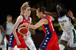 United States' Diana Taurasi (12), center, is fouled by Nigeria's Ify Ibekwe (52) during women's basketball preliminary round game at the 2020 Summer Olympics, Tuesday, July 27, 2021, in Saitama, Japan. (AP Photo/Charlie Neibergall)