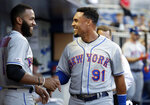 New York Mets right fielder Carlos Gomez (91) talks with shortstop Amed Rosario before the team's baseball game against the Miami Marlins, Friday, May 17, 2019, in Miami. (AP Photo/Lynne Sladky)