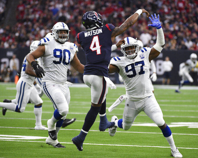 Houston Texans quarterback Deshaun Watson (4) is pressured by Indianapolis Colts defensive tackle Grover Stewart (90) and defensive tackle Al-Quadin Muhammad (97) during the first half of an NFL wild card playoff football game, Saturday, Jan. 5, 2019, in Houston. (AP Photo/Eric Christian Smith)