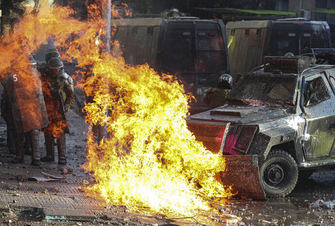 A petrol bomb explodes in front of a police vehicle during clashes with anti-government demonstrators in Santiago, Chile, Tuesday, Nov. 12, 2019. Students in Chile began protesting nearly a month ago over a subway fare hike. The demonstrations have morphed into a massive protest movement demanding improvements in basic services and benefits, including pensions, health, and education. (AP Photo/Esteban Felix)