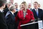 Dayton, Ohio Mayor Nan Whaley, center, greets Ohio Gov. Mike DeWine before speaking during a news conference Monday, Oct. 7, 2019 at the Ohio Department of Public Safety in Columbus, Ohio. Republican Gov. Mike DeWine's new proposals to address Ohio gun violence in the wake of the Dayton mass shooting don't include background-check requirements for gun sales or a so-called red-flag law to restrict firearms for people perceived as threats, despite his earlier support of those ideas. Instead, his administration detailed legislative proposals Monday intended to increase and improve background checks and ensure people don't have firearms if a court has deemed them to be a danger. (Joshua A. Bickel/The Columbus Dispatch via AP)