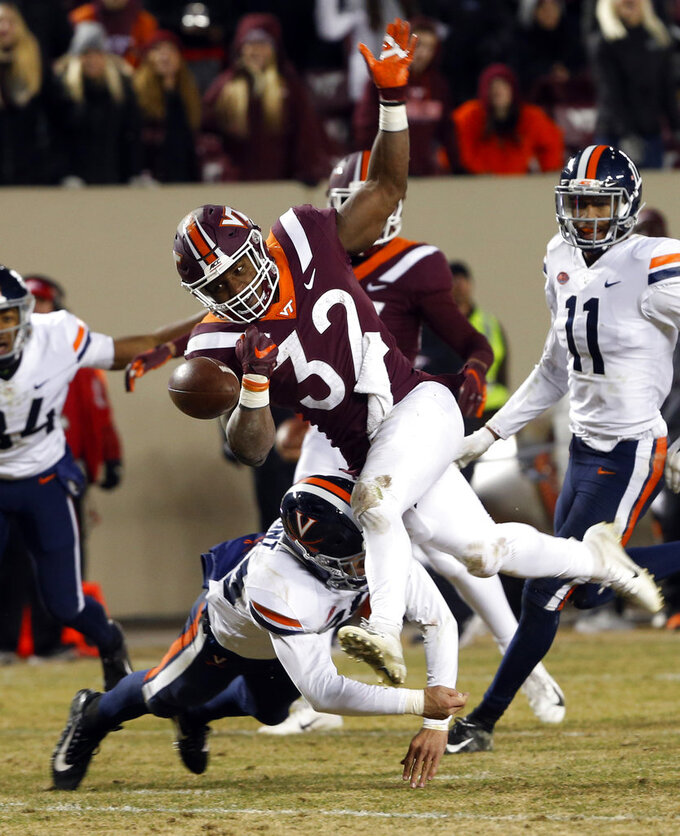 Virginia running back Lamont Atkins (25) tackles Virginia Tech running back Steven Peoples (32) near the end zone as he loses the ball during the second half of an NCAA college football game in Blacksburg, Va., Friday, Nov. 23, 2018. Virginia Tech defeated Virginia 34-31. (AP Photo/Steve Helber)