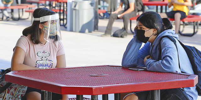 The second first day of school two students wearing protective face coverings have a conversation before the start of the first class during the coronavirus pandemic on the Gila Ridge High School campus, Thursday morning, Sept. 17, 2020, in Yuma, Ariz. (Randy Hoeft/The Yuma Sun via AP)