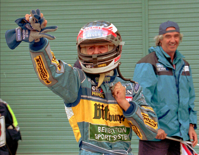 FILE - In this Oct. 29, 1995, fie photo, German driver Michael Schumacher waves to the crowd in front of his team manager Flavio Briatore after getting off his Benetton-Renault following his victory in the Japanese Grand Prix at the Suzuka Circuit, Japan. Against the backdrop of celebrations marking Michael Schumacher's 50th birthday Thursday, Jan. 3, 2019, the medical condition of Formula One's most successful driver remains just as fiercely guarded by his close family. (AP Photo/Naokazu Oinuma, File)