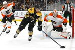 Boston Bruins' Anders Bjork (10) controls the puck in front of Philadelphia Flyers' Carter Hart (79) during the first period of an NHL hockey game in Boston, Sunday, Nov. 10, 2019. (AP Photo/Michael Dwyer)