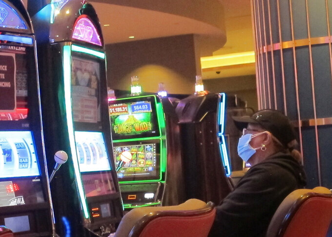 This May 3, 2021 photo shows an intentionally disabled slot machine next to a woman playing a different slot machine while wearing a face mask at the Hard Rock casino in Atlantic City, N.J. On Friday, May 28,  New Jersey dropped its indoor mask mandate and Atlantic City casinos turned slot machines that were disabled to create distance between players back on again. (AP Photo/Wayne Parry)