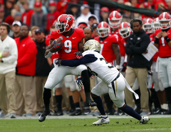 Georgia wide receiver Jeremiah Holloman (9) is brought down by Georgia Tech defensive back Jaytlin Askew (33) after a catch in the first half of an NCAA college football game Saturday, Nov. 24, 2018, in Athens, Ga. (AP Photo/John Bazemore)
