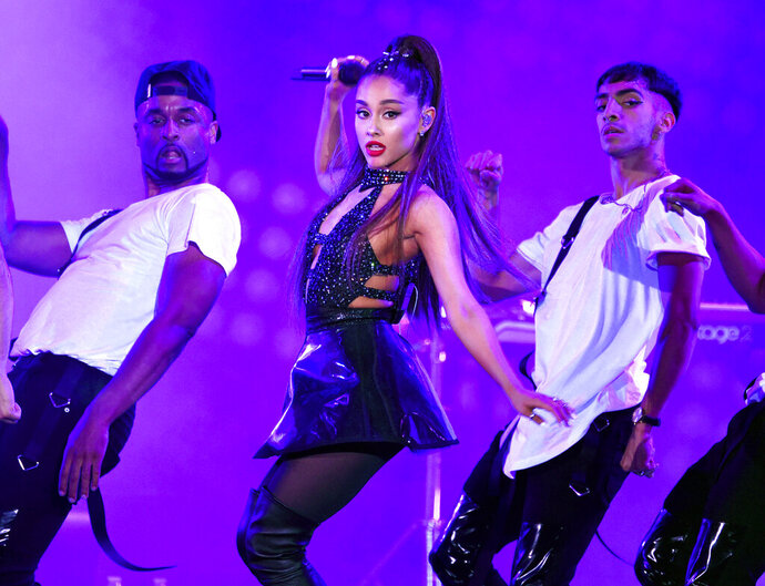 """FILE - In this June 2, 2018 file photo, Ariana Grande, center, performs at Wango Tango in Los Angeles. Grande won her first Grammy Award on Sunday, Feb. 10, but the singer didn't collect it after she decided to skip the ceremony following a public dispute with the show's producer. She won best pop vocal album for """"Sweetener,"""" beating Taylor Swift, Kelly Clarkson, Pink, Shawn Mendes and Camila Cabello in the category. Grande was not in attendance at the pre-telecast ceremony, but she wrote on Twitter that her win was """"wild and beautiful."""" (Photo by Chris Pizzello/Invision/AP, File)"""