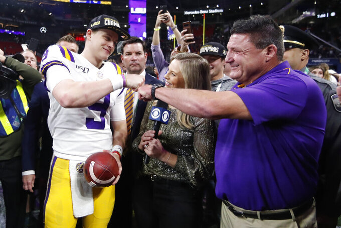 FILE - In this Dec.  7, 2019, file photo, LSU quarterback Joe Burrow and LSU head coach Ed Orgeron celebrate after the Southeastern Conference championship NCAA college football game against Georgia, in Atlanta. Orgeron is The Associated Press Coach of the Year after leading the top-ranked Tigers to a Southeastern Conference championship and their first College Football Playoff appearance.(AP Photo/John Bazemore, File)