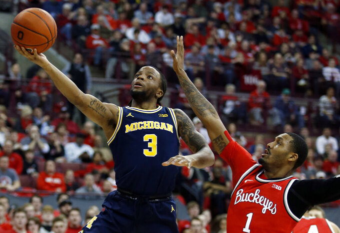 Michigan guard Zavier Simpson, left, goes up to shoot in front of Ohio State guard Luther Muhammad during the first half of an NCAA college basketball game in Columbus, Ohio, Sunday, March 1, 2020. (AP Photo/Paul Vernon)