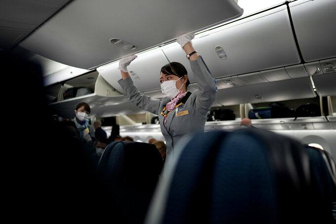 A flight attendant closes the overhead compartment on a flight to Tokyo from Frankfurt, Germany, Sunday, July 18, 2021. (AP Photo/Natacha Pisarenko)