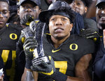 Oregon running back CJ Verdell holds the MVP trophy after Oregon defeated Utah 37-15 in an NCAA college football game for the Pac-12 Conference championship in Santa Clara, Calif., Friday, Dec. 6, 2018. (AP Photo/Tony Avelar)