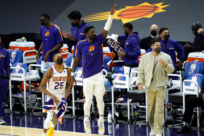 Phoenix Suns center Deandre Ayton, center, guard Devin Booker, right, and forward Mikal Bridges (25) cheer during the second half of the team's NBA basketball game against the Golden State Warriors, Thursday, Jan. 28, 2021, in Phoenix. (AP Photo/Matt York)