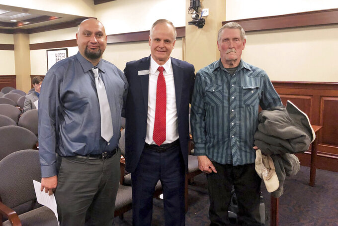 FILE - In this Feb. 11, 2020, file photo, from left, Christopher Tapp, Republican Rep. Doug Ricks and Charles Fain appeared before the Idaho House Judiciary, Rules and Administration Committee in Boise, Idaho, to testify in favor of legislation that would compensate the wrongly convicted. Idaho officials have approved payments of $1.4 million to Fain and $1.2 million to Tapp, who each spent decades in prison for crimes they didn't commit. Republican Gov. Brad Little and three other statewide-elected members of the Idaho Board of Examiners on Tuesday, June 15, 2021, approved the payments to Fain and Tapp. (AP Photo/Keith Ridler, File)