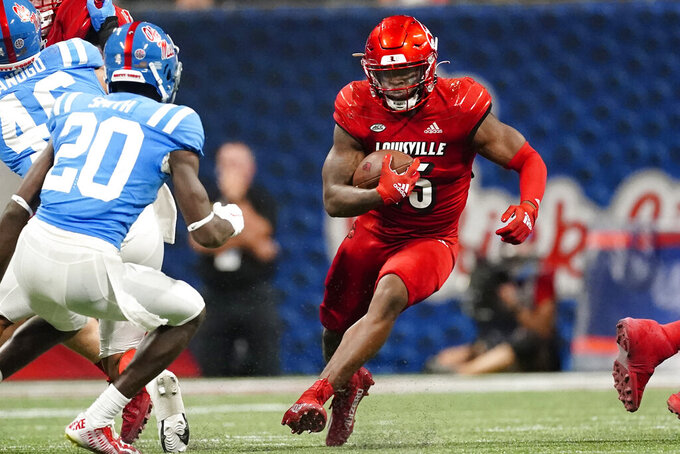 Louisville running back Jalen Mitchell (15) runs up the middle as Mississippi defensive back Keidron Smith (20) moves in during the second half of an NCAA college football game Monday, Sept. 6, 2021, in Atlanta. (AP Photo/John Bazemore)
